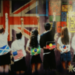 Harmony poster - Students raising right arm as they face large flags